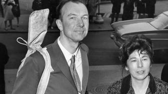 FILE - In this April 4, 1961, file photo, Pete Seeger, with a banjo slung over his shoulder, is accompanied by his wife, Toshi, as he arrives at the federal court in New York for sentencing on a conviction for contempt of Congress. The Federal Bureau of Investigation released more than 1,700 pages of documents it collected on the folk singer. (AP Photo)