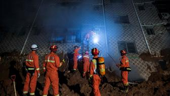 SHENZHEN, CHINA - DECEMBER 20:  Emergency services search a collapsed building after a landslide buried 22 buildings on December 20, 2015 in Shenzhen, China. Reports say at least 27 people are missing and 7 people have been rescued so far after a landslide hit China's southern province on Sunday.  (Photo by Lam Yik Fei/Getty Images)
