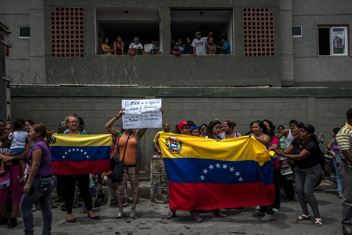 Residents of the Algodonal neighborhood hold national flags and cheer as they watch Venezuelan soldiers take over a warehouse
