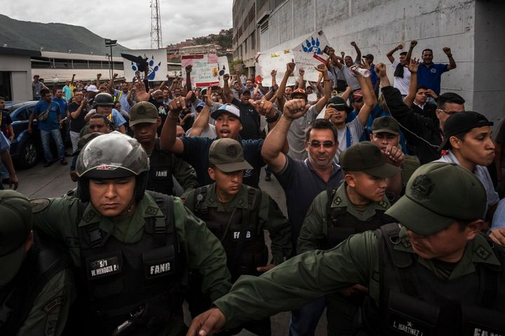 Workers at a food distribution center in Caracas react after Venezuelan soldiers took over their warehouse in July.