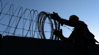 To go with Afghanistan-unrest-US-Bagram,FEATURE by Emmanuel PARISSE In this photograph taken on November 1, 2014, a US soldier removes barbed wire from a wall in Bagram Air Base, some 50 kms north of Kabul. First they remove the power supply, then they tear out fixtures by hand, before a mechanical digger destroys the roof in a cloud of dust -- the US military is ending its war in Afghanistan and the wrecking crews are busy. AFP PHOTO/Wakil KOHSAR        (Photo credit should read WAKIL KOHSAR/AFP/Getty Images)