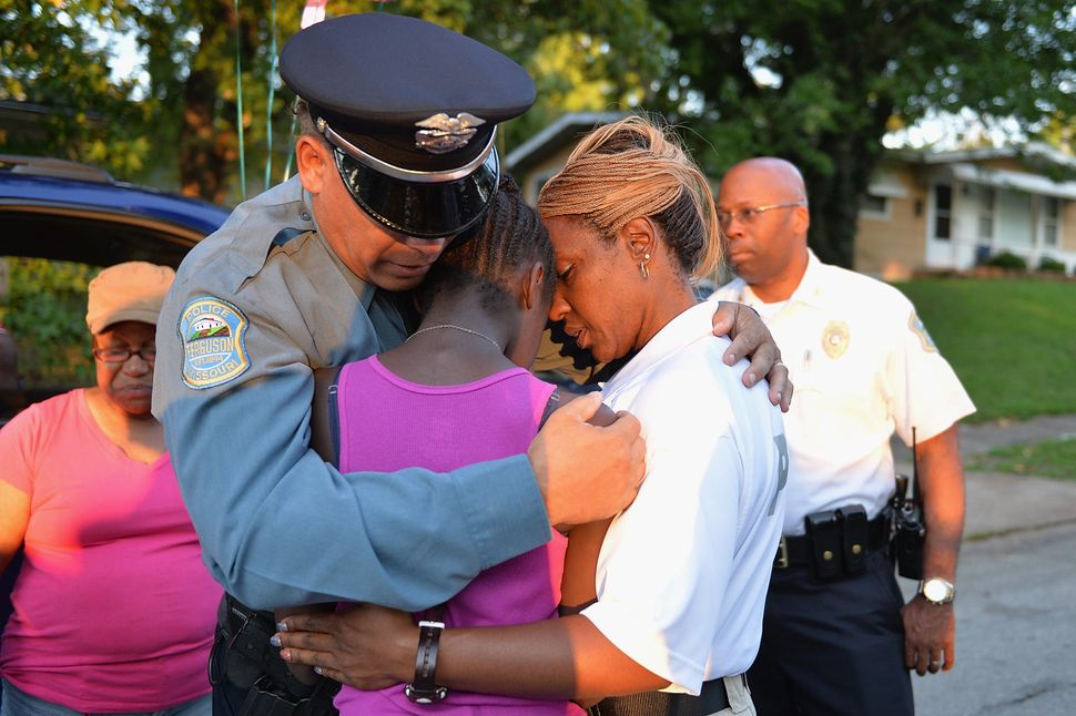 Police officers Greg Casem and Dominica Fuller console a child at a candlelight vigil held in honor of Jamyla Bolde