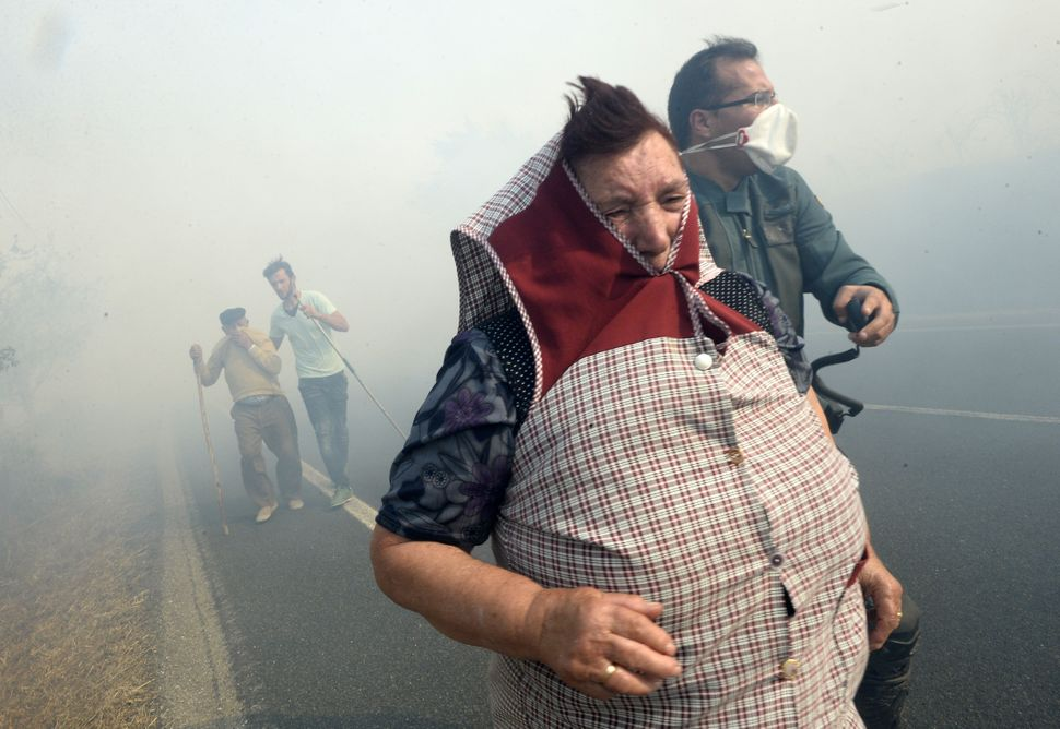 "A Spanish Civil Guard officer helps villagers during a <a href=""http://www.theguardian.com/world/gallery/2015/aug/31/wildfire"