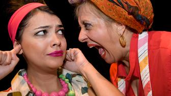 Close-up of a mature woman shouting and her daughter sticking fingers in her ears
