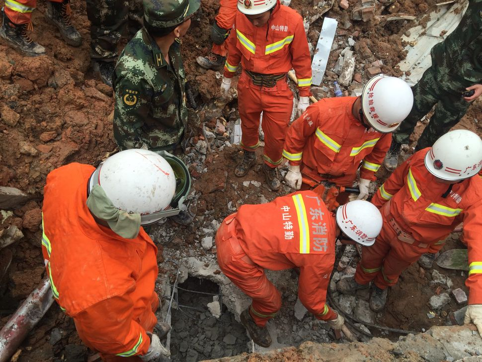 Rescuers search for survivors in the rubble from collapsed buildings.