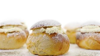 Home made traditional Swedish easter bun with almond filling and sweet whipped cream, isolated on white