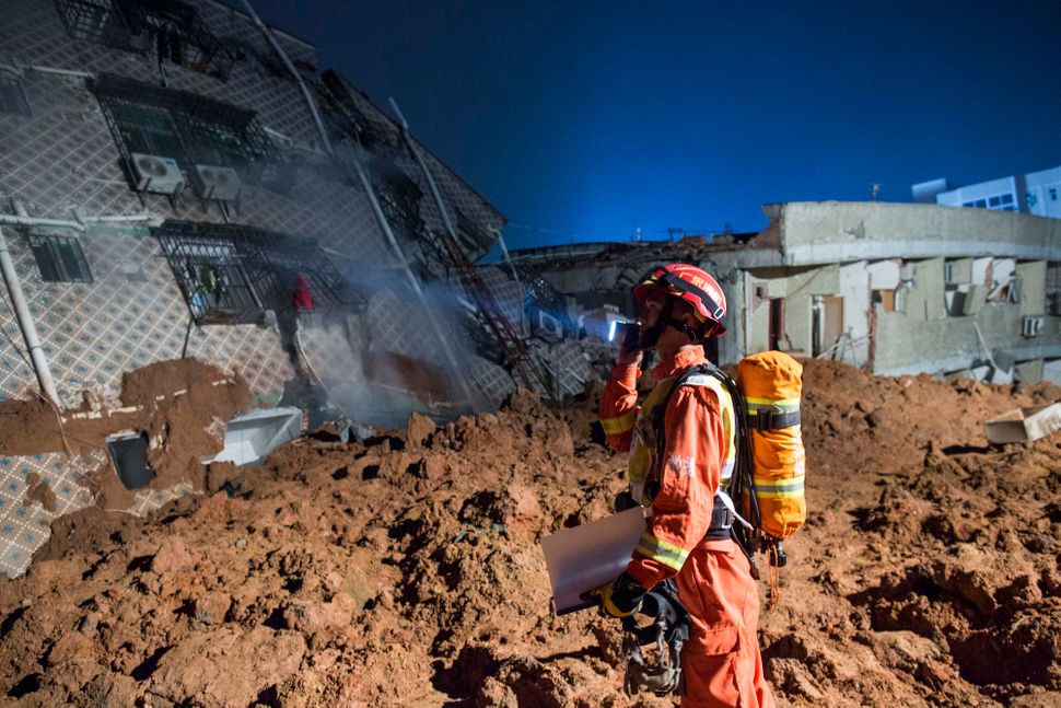 Emergency services search a collapsed building after the landslide buried dozens of buildings.