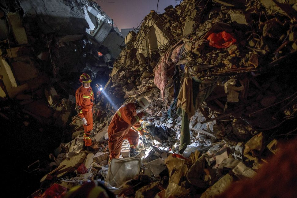 Rescuers work their way through the ruined buildings.
