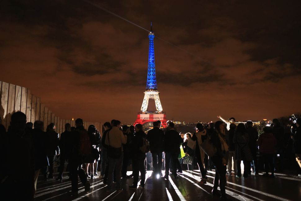 "The Eiffel Tower is illuminated in the colors of the French flag after at least 130 people from <a href=""https://www.huffpost"