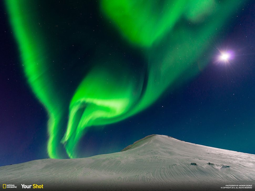 The aurora borealis shares the sky with a bright moon in Iceland. Named for the Roman goddess of dawn, the vivid beams of lig