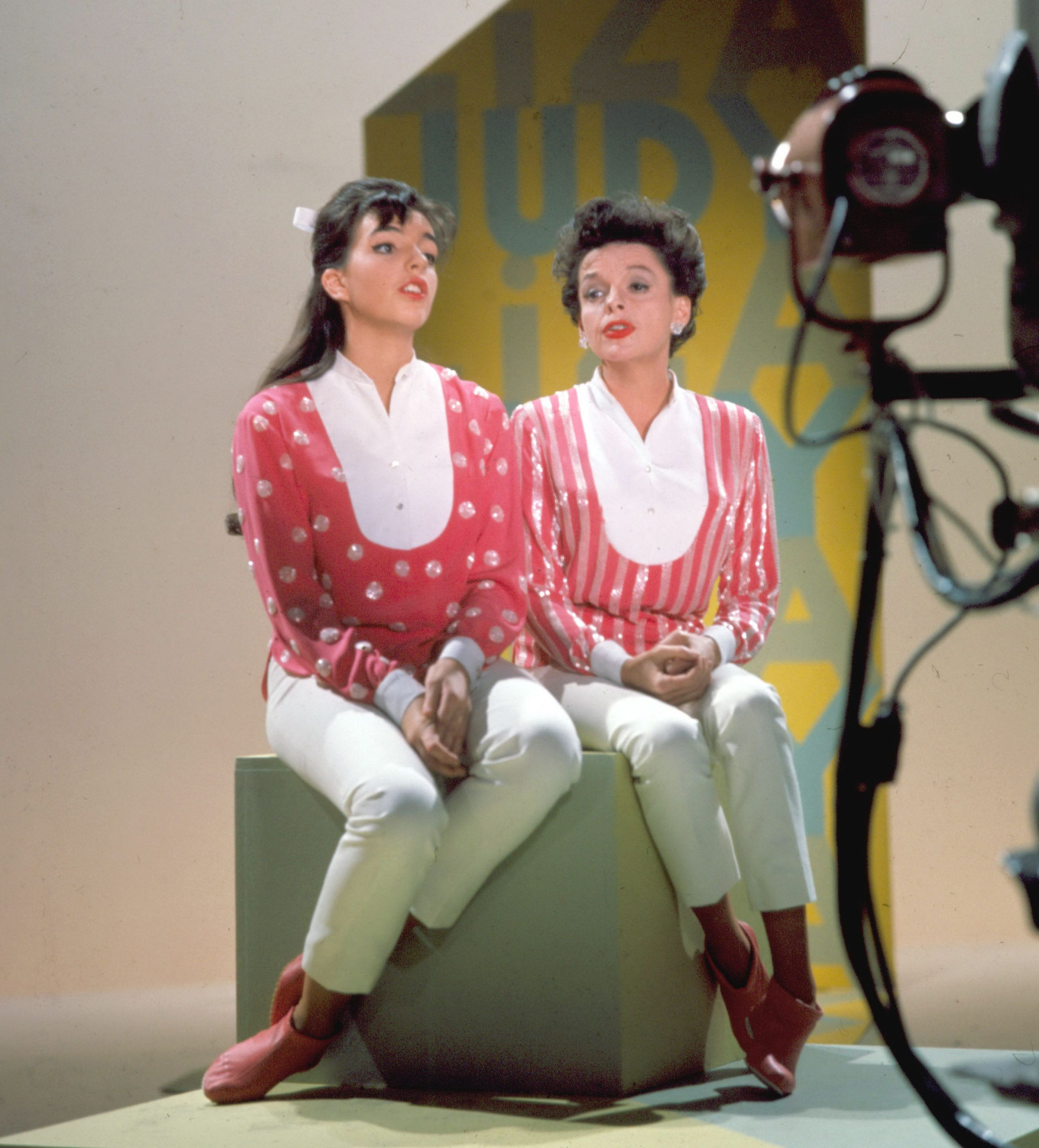 American singer and actress Judy Garland (right) (1922 - 1969) and her daughter, singer and actess Liza Minnelli sit together on a stage cube on top of a raised platform and sing a duet on the set of the CBS music variety series 'The Judy Garland Show,' CBS Television City, Los Angeles, California, July 16, 1963. Garland and Minnelli wear nearly matching outfits and sit in front of a backdrop with their names printed on it. (Photo by CBS Photo Archive/Getty Images)