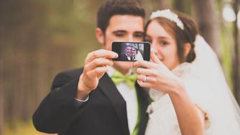 This modern wedding shot incorporates some of the social media fixation of the current generation.  The culture emphasizes sharing the moment, and this wedding photo of a couple taking a 'selfie' tells a story.