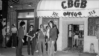 American musician Lenny Kaye, of the Patti Smith Group, takes a break outside CBGB on the Bowery, New York, New York, May 28, 1977. (Photo by Allan Tannenbaum/Getty Images)