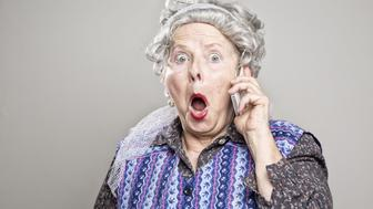senior woman stereotypical housewife, talking on mobile phone, surprised or shocked by what she is hearing