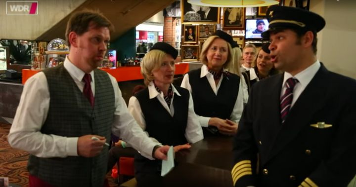 Singers dressed like a pilot and a waiter are seen breaking into song among several flight attendants who appear stunned.