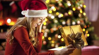 Beautiful blonde young woman wearing Santa's hat is opening Christmas presents.