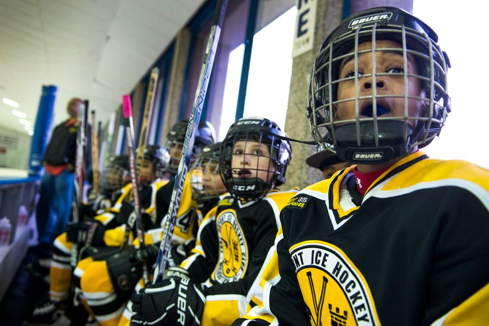 Players in the Fort Dupont Ice Hockey Club watch a game from the bench in March 2014.