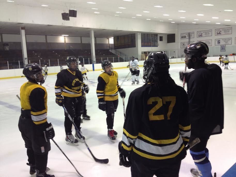 Duante' Abercrombie, right, instructs players in the Fort Dupont Ice Hockey Club during a practice in Dec. 2014. Abercrombie