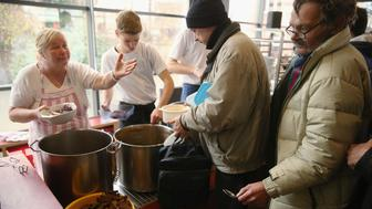 BERLIN, GERMANY - DECEMBER 15:  Volunteers serve a hearty lunch at the soup kitchen at the Franciscan monastery in Pankow district on December 15, 2015 in Berlin, Germany. The facility serves the needy with hundreds of meals a day, donated clothing and social services. German President Joachim Gauck visited the soup kitchen earlier in the day.  (Photo by Sean Gallup/Getty Images)