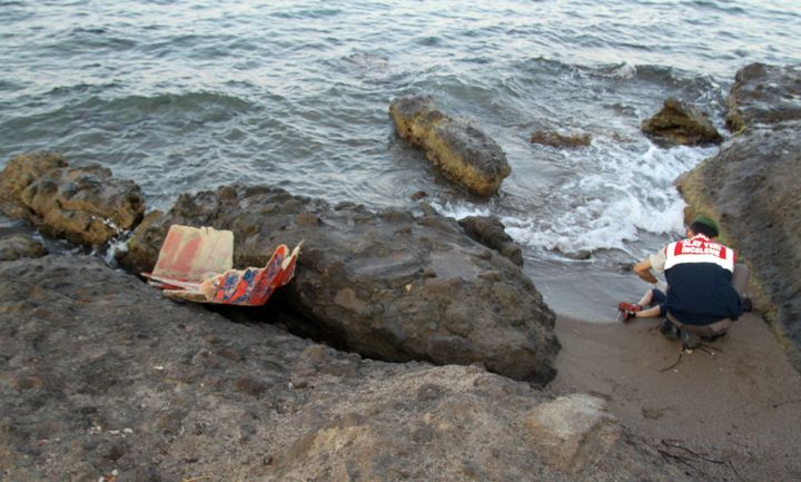 A Turkish gendarmerie soldier movesAlan Kurdi's body, which washed ashore on a beach after a boat carrying 12 migrants