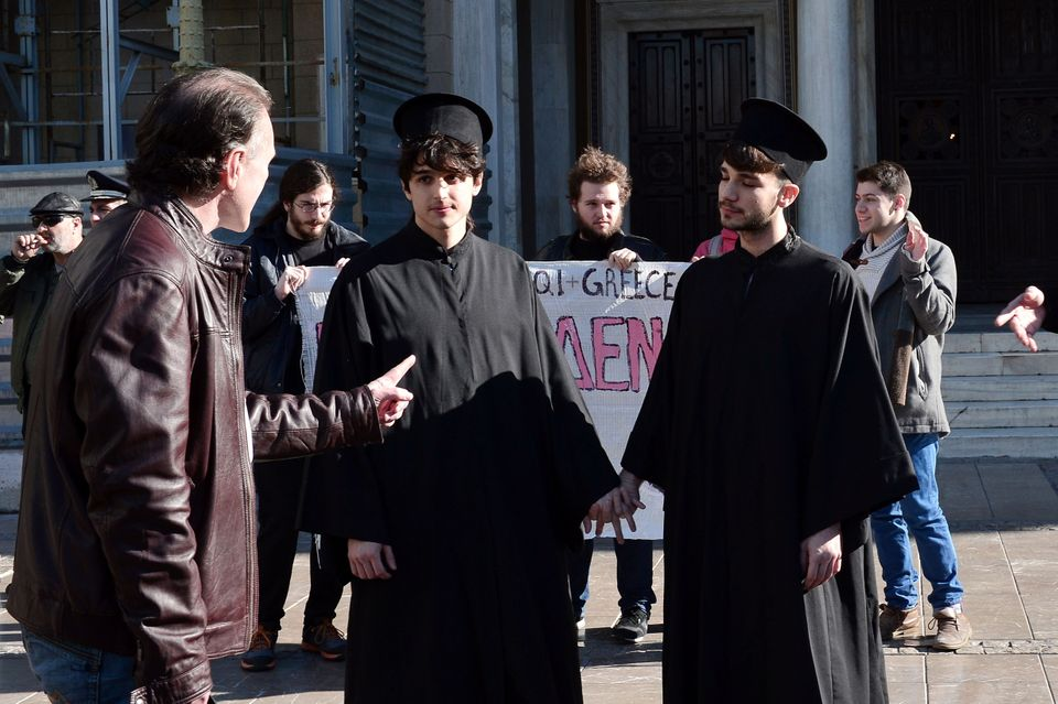 Gay rights activists dressed up as Orthodox priests speak with a man next to the Metropolitan church in Athens on December 22