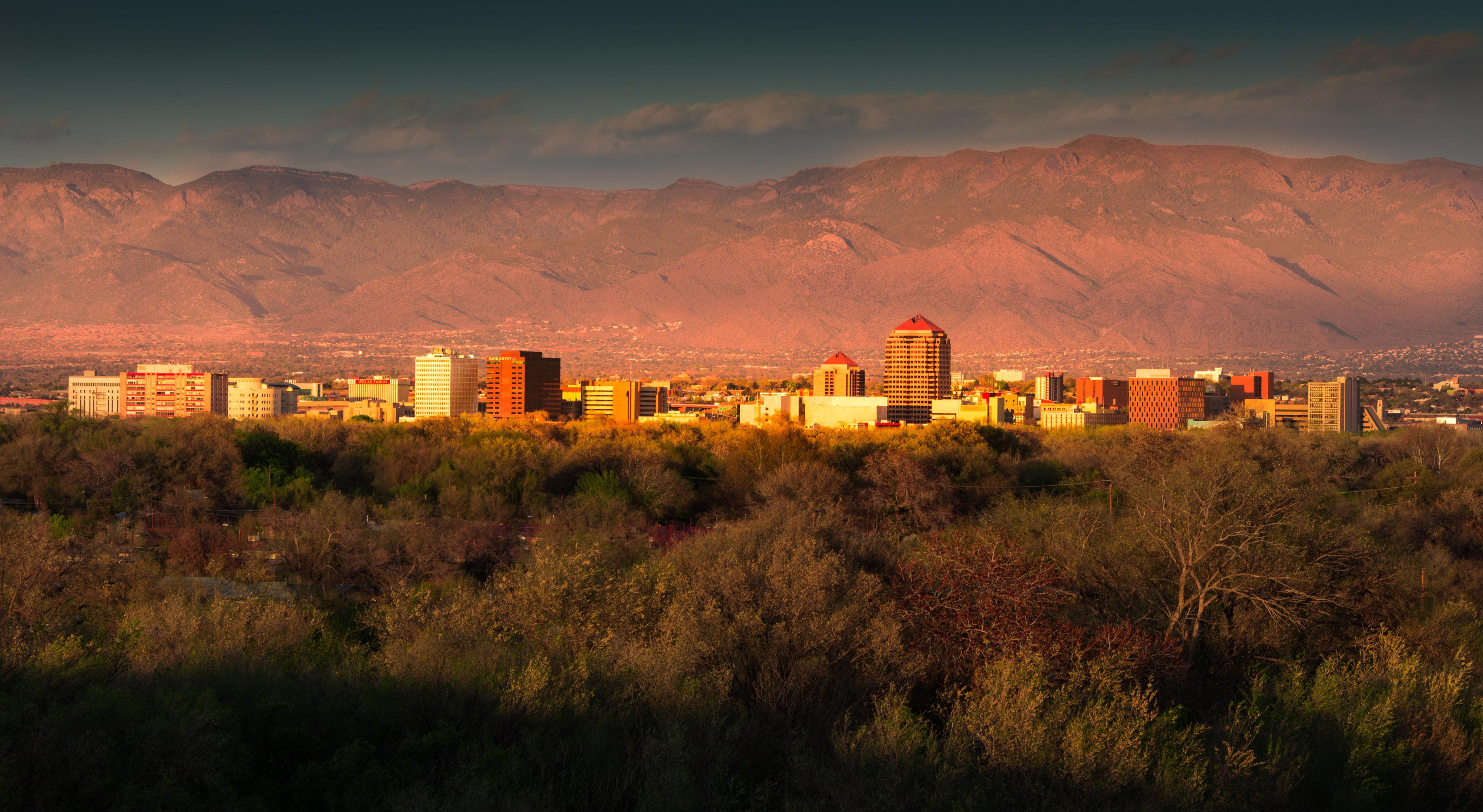 Albuquerque skyline at sunset, downtown buildings, Sandia Peak in background.