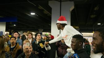 BLOOMINGTON, MN -  DECEMBER 23:  Dwight D. Campbell, wearing a santa hat, fist bumps passers by who are being pushed out of the Mall of America by police on to the Lightrail on December 23, 2015 in Bloomington, Minnesota. Campbell, on break from his job at the mall, came to support the protest.  Black Lives Matter Minneapolis staged a brief protest at the Mall of America in Bloomington, MN before moving their protest to the airport. (Photo by Stephen Maturen/Getty Images)