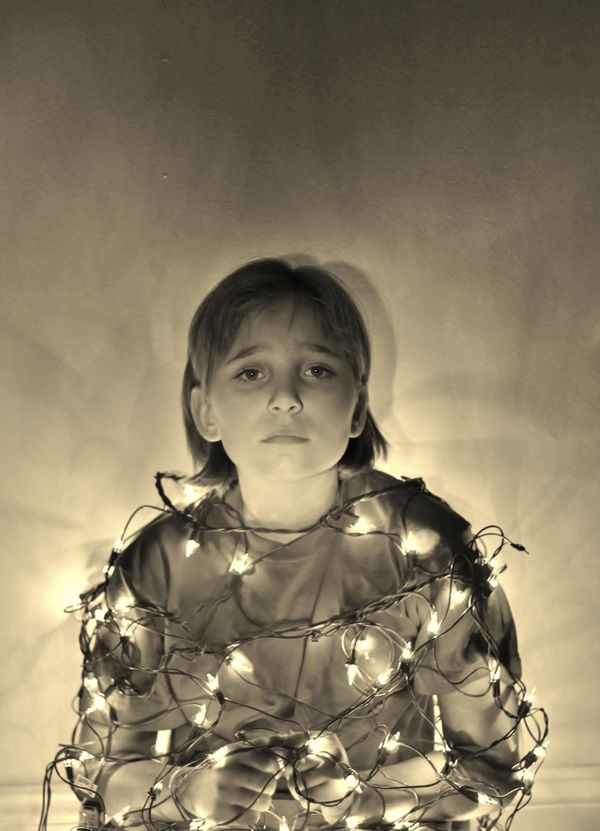 She's sad because its so much harder to open presents when restrained by a tangle of Christmas lights.