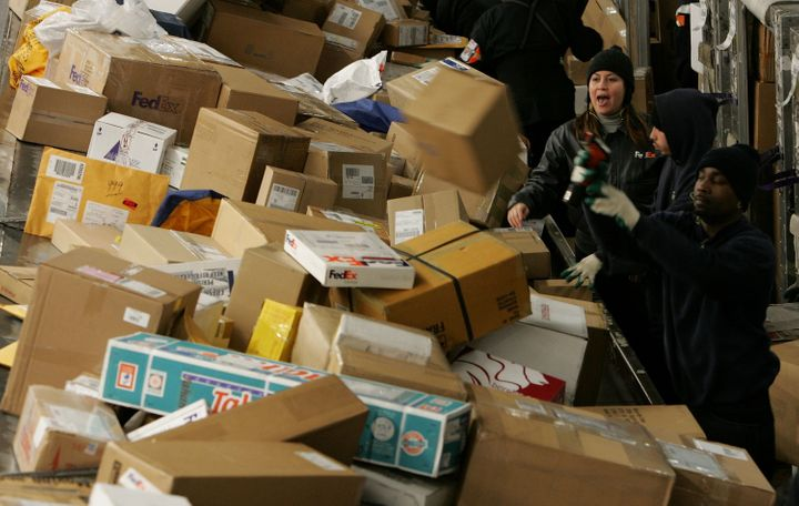 FedEx workers sort through a pile of boxes at the FedEx sort facility at the Oakland International Airport, Dec. 18, 2006, in
