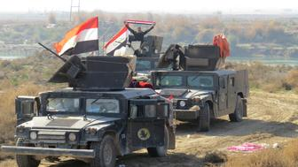 Iraqi pro-government forces hold their national flags on armored vehicles as they take position in al-Aramil area, south of the Anbar province's capital Ramadi, during military operations on December 22, 2015. Iraqi security forces advanced into the centre of the city for a final push aimed at retaking the city they lost to the Islamic State jihadist group in May 2015.   AFP PHOTO / STR / AFP / -        (Photo credit should read -/AFP/Getty Images)