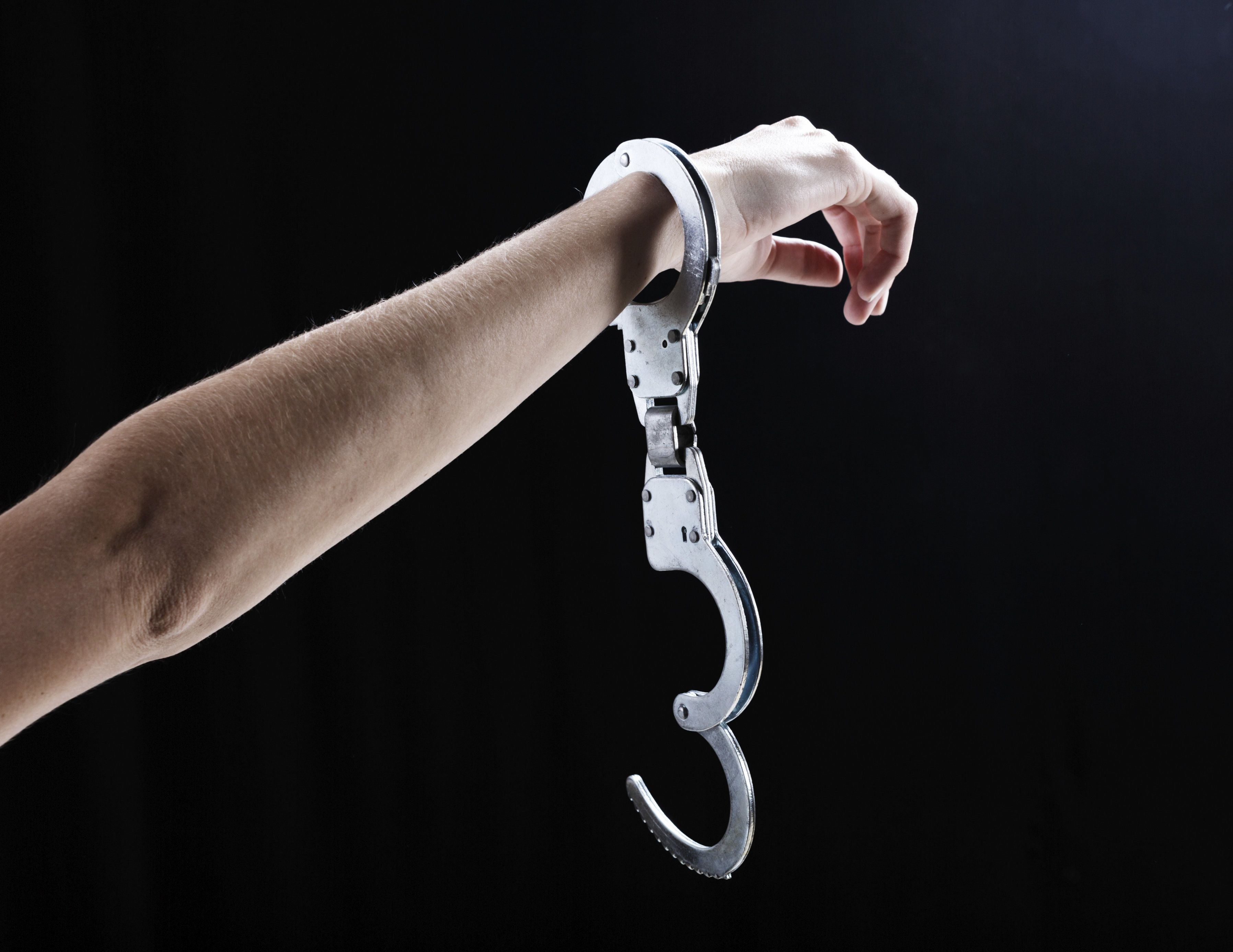 A woman's hand, holding up a hand wearing a single, open handcuff  against a black bakcground. Symbolic of release or freedom from almost anything!