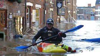 YORK, UNITED KINGDOM - DECEMBER 27: A canoeist paddles along flooded streets in York city centre, United Kingdom on December 27, 2015. Heavy rain caused the river Ouse to burst it's banks on Boxing Day, with many homes being evacuated overnight on the British annual Christmas holiday. (Photo by Lindsey Parnaby/Anadolu Agency/Getty Images)