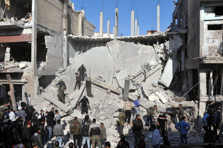 Syrians check the rubble at the site of two car bomb attacks in the al-Zahraa neighborhood of the central Syrian city of Homs
