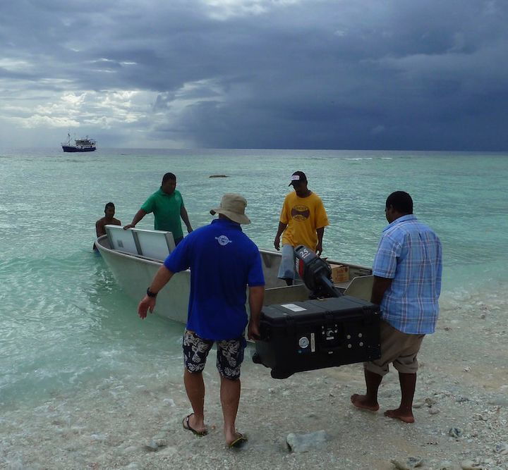 Workers deliver a solar-powered desalination machine to one of the outer islands.