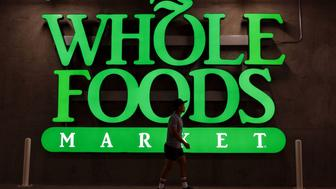 A pedestrian walks past Whole Foods Market Inc. signage is displayed outside of the new store in downtown Los Angeles, California, U.S., on Monday, Nov. 9, 2015. Located beneath the recently opened Eighth & Grand residences, the 41,000-square-foot store features a juice bar, fresh poke, expanded vegan options in all departments, a coffee bar (with cold brew on tap), more than 1,000 hand-picked wines, home delivery via Instacart and bar-restaurant The Eight Bar. Photographer: Patrick T. Fallon/Bloomberg via Getty Images