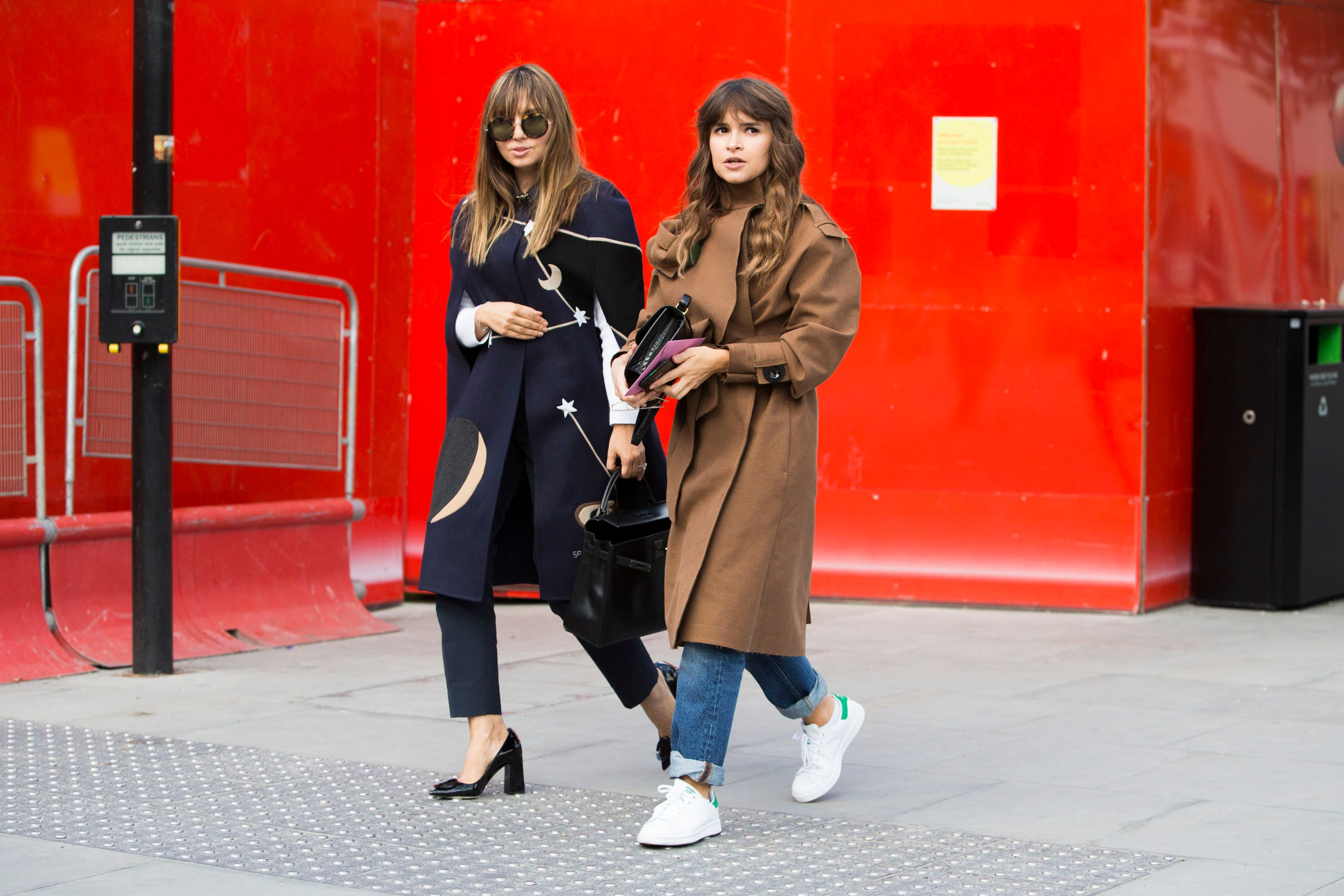 LONDON, ENGLAND - SEPTEMBER 19:  Nasiba Adilova and Miroslava Duma exit a show during London Fashion Week Spring Summer 2016 at Kings Cross on September 19, 2015 in London, England Nasiba wears a blue Valentino cape with planets and stars. Miroslava Duma wears a brown AWAKE trench coat, Hermes purse, and white Adidas Stan Smith sneakers.  (Photo by Melodie Jeng/Getty Images)