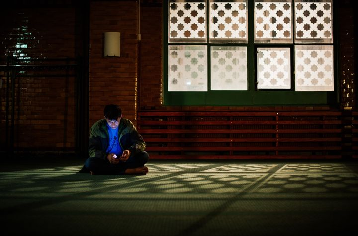 A refugee checks his cell phone at the prayer hall after arriving to Stockholm central mosque on Oct. 15, 2015.