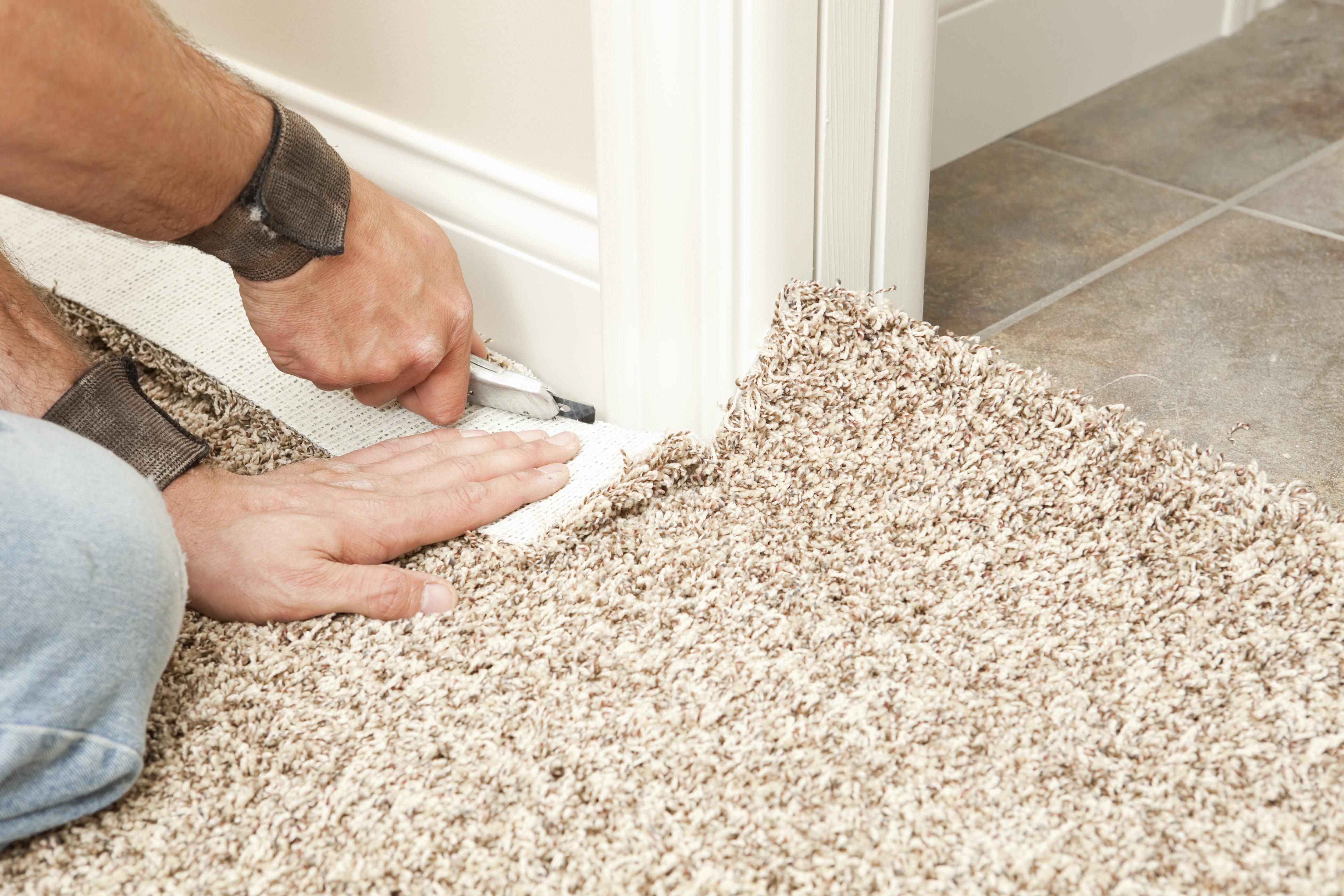 Carpet Installer Using Knife to Trim Wall Edge
