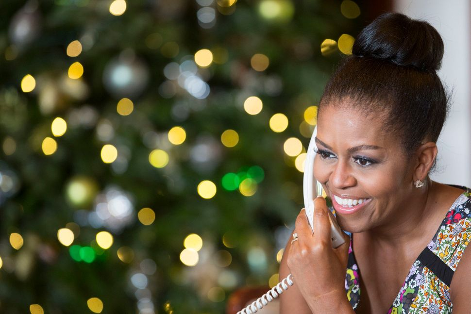 First lady Michelle Obama reacts while talking on the phone to children across the country as part of the annual NORAD Tracks