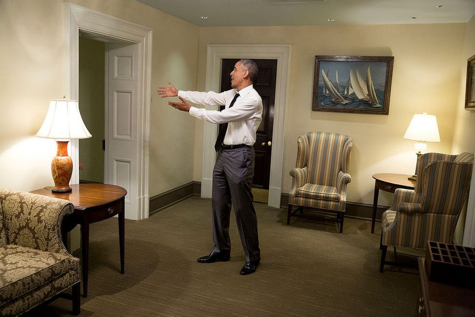 President Barack Obama gestures to a departing guest in a hallway of the West Wing of the White House on April 29, 2015.