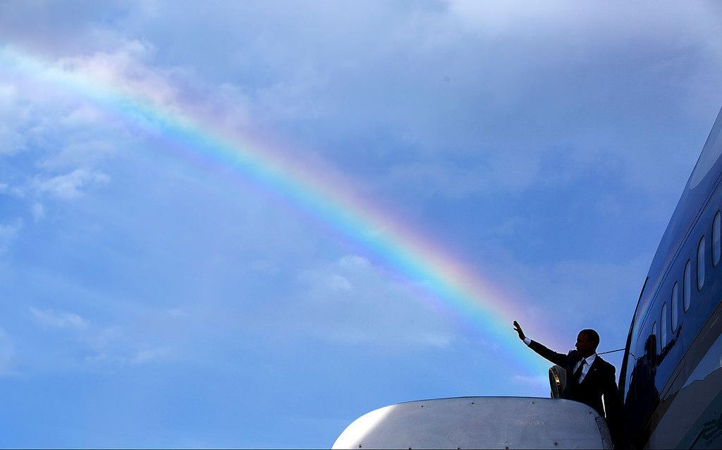 President Barack Obama's wave aligns with a rainbow as he boards Air Force One at Norman Manley International Airport before