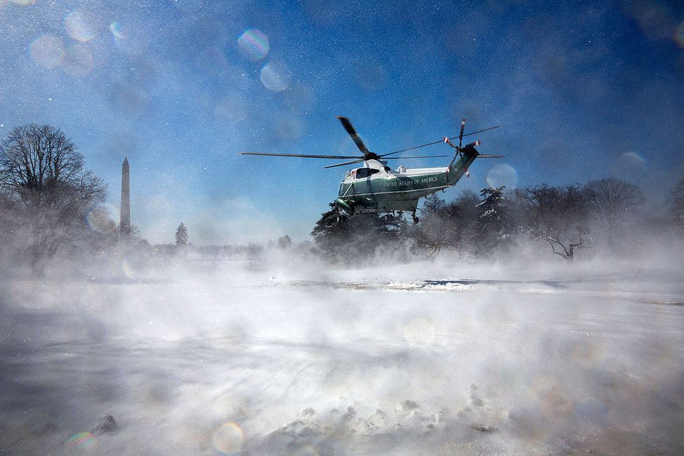 Snow disperses as Marine One takes off from the South Lawn of the White House on March 6, 2015.