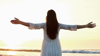 Rear view of young woman with arms outstretched on shore. Carefree female is enjoying nature against clear sky. Woman in white sundress is standing on beach during sunset.