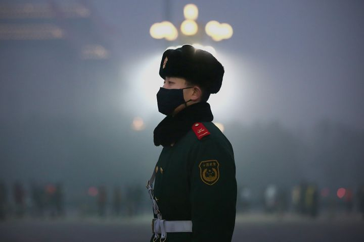 A Chinese paramilitary policeman wears a mask to protect against pollution as he guards during heavy pollution day in Tiananm
