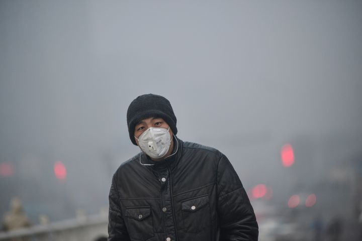 A pedestrian walks along a street in heavy smog in Tianjin, China.
