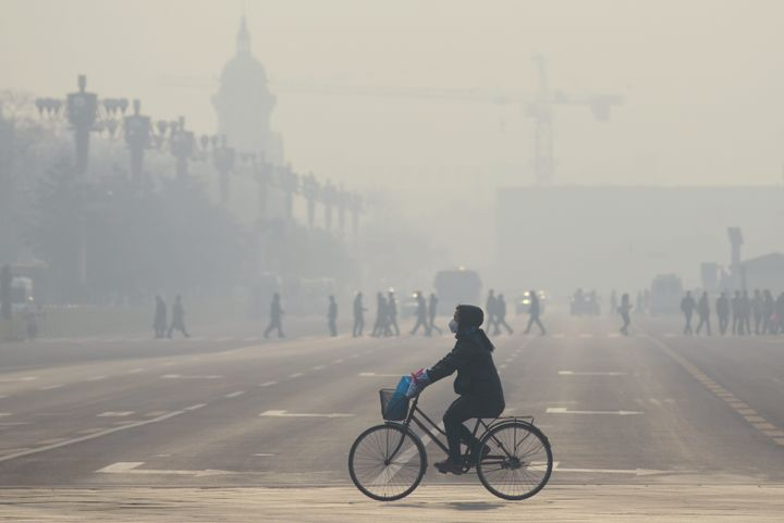 A woman wears a mask as she rides her bicycle near Tiananmen Square on the third day of a 'red alert' for pollution in Beijin