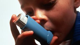 Young boy (6-8) using asthma inhaler, close-up