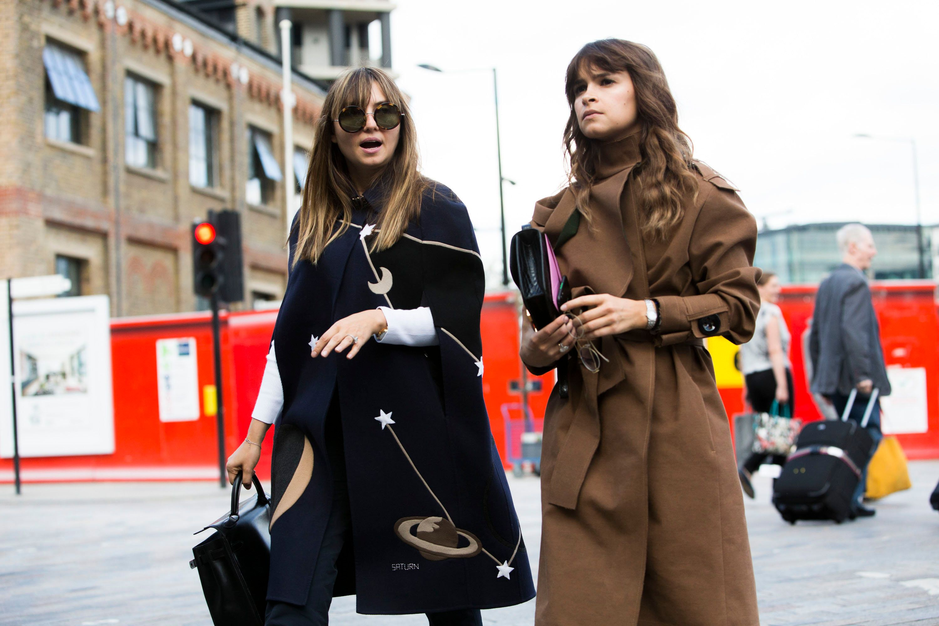 LONDON, ENGLAND - SEPTEMBER 19:  Nasiba Adilova wears a blue Valentino cape with planets and stars while Miroslava Duma wears a brown AWAKE trench coat and Hermes purse during London Fashion Week Spring Summer 2016 at Kings Cross on September 19, 2015 in London, England  (Photo by Melodie Jeng/Getty Images)