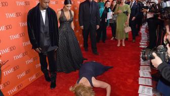 Honoree and Comedian Amy Schumer pretends to trip and fall on the floor  in front of honorees Kim Kardashian (2nd-L) and Kanye West (L) as they attend the Time 100 Gala celebrating the Time 100 issue of the Most Influential People at  The World at Jazz at Lincoln Center on April 21, 2015 in New York.  AFP PHOTO /  TIMOTHY  A. CLARY        (Photo credit should read TIMOTHY A. CLARY/AFP/Getty Images)