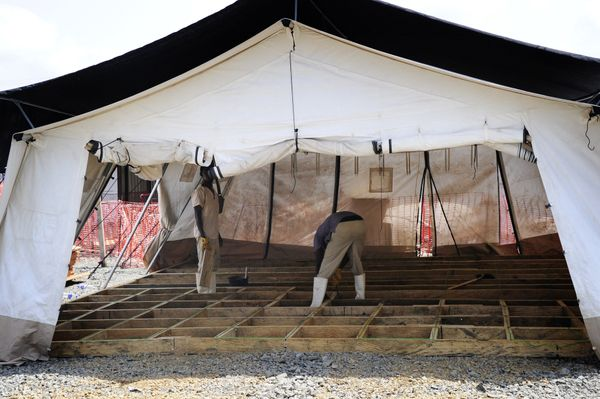 Liberian workers dismantle shelters in an Ebola treatment center closed by the charity Medecins Sans Frontiers (or Doctors Wi